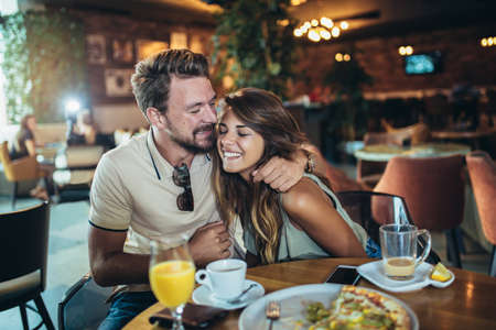 Young happy couple eating pizza in a restaurant