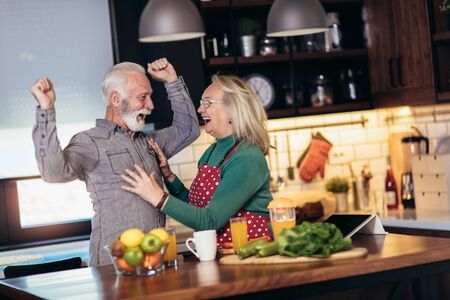 Beautiful senior couple is dancing and smiling while cooking together in kitchen. Quarantine. Health concept. Banco de Imagens