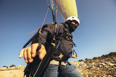 Active senior paraglider on the ground prepairs to fly. 版權商用圖片