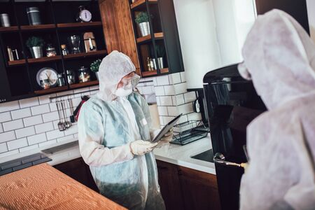 Specialists in protective suits take samples from surfaces in the home to test for a new corona virus. Stock Photo