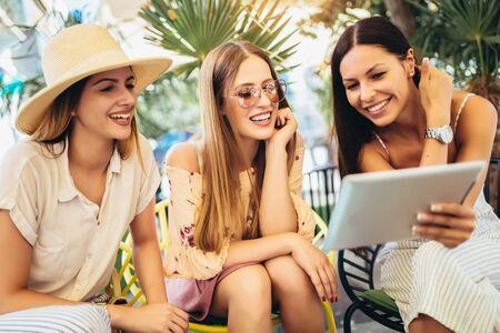 Drei schöne Freunde in einem Café mit digitalem Tablet und Spaß