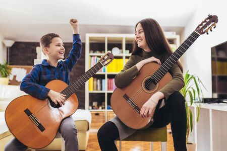 Brother and sister playing guitar at home and having fun.