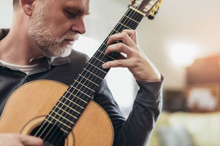 Handsome mature man in casual clothes is smiling while playing guitar at home Standard-Bild