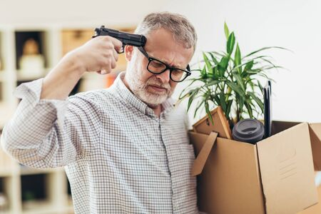 Frustrated man while coming home with a heavy box full of personal items after losing his job using gun to kill himself Stok Fotoğraf