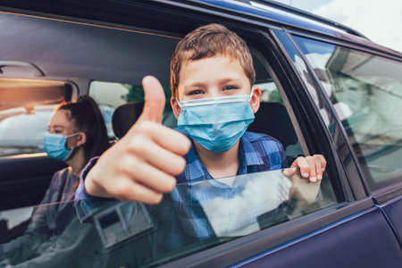 Kids wearing anti virus masks and using digital tablets in the car. Kids are travelling in car during coronavirus outbreak