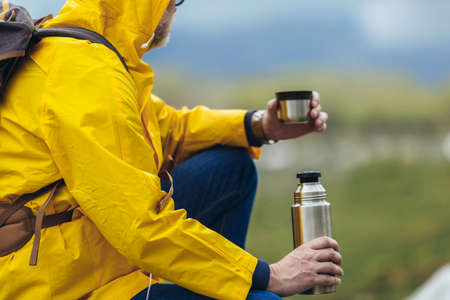 Middle age man with backpack taking break of hiking in a beautiful nature and taking tea or water from a  flask