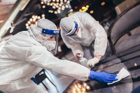 Professional workers in hazmat suits disinfecting indoor of cafe or restaurant, pandemic health risk, coronavirus Archivio Fotografico