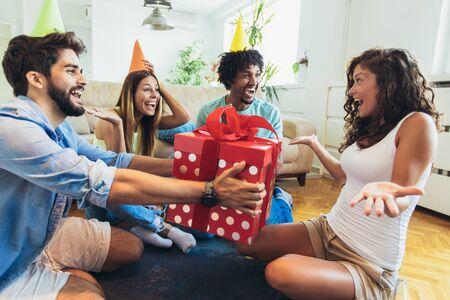 Jeune groupe d'amis heureux célébrant l'anniversaire à la maison.