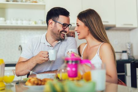 Young happy couple sitting in modern apartment and having breakfast together. Imagens