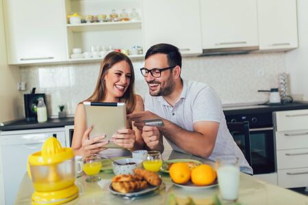 Couple spending money online on the internet, and having breakfast in the kitchen.