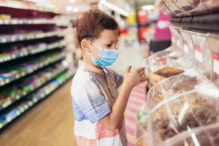 A new normal. Caucasian boy in sanitary face mask shopping sweets. Child wearing protective mask against coronavirus. Safety, health protection during covid-19 quarantine.