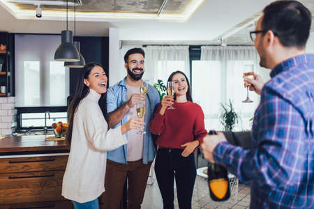 Young people cheering with champagne flutes and looking happy while having home party.