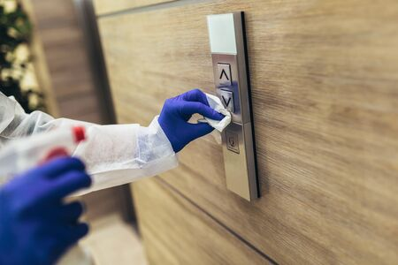 Staff using disinfectant from the bottle spraying an elevator push button control panel. Disinfection ,cleanliness and healthcare,Anti Corona virus (COVID-19). 免版税图像