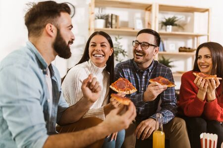 Group of young friends eating pizza in home interior. Young people having fun together.