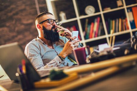 Young man sitting in office with a cup of coffee,smoking cigarrette