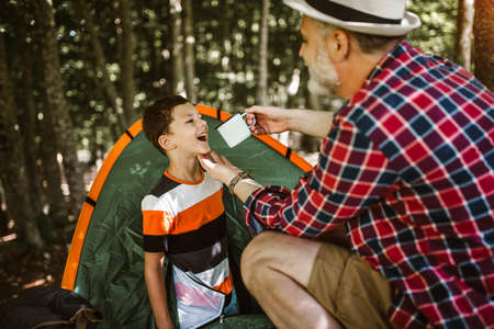 Boy camping with grandfather in the forest. Banque d'images