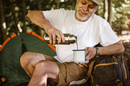 Man camping in nature taking rest and drinking fresh coffee