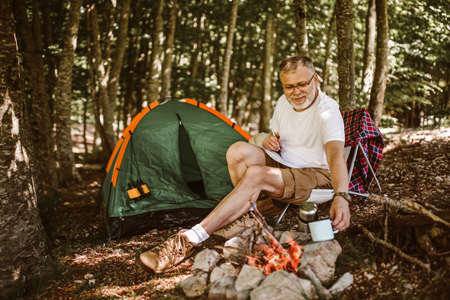 Mature man sitting in front of a tent and near campfire and writing in a notebook.