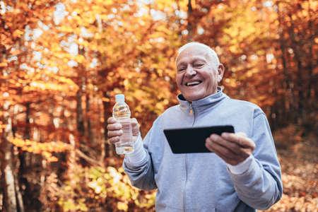 Senior Man Exercising In Park, having fun using digital tablet