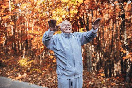 Senior Man Exercising In Park, having fun Фото со стока