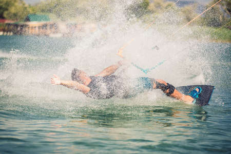 Professional kiter makes the difficult trick on a river. Kitesurfing Kiteboarding action photos man among waves quickly goes Stok Fotoğraf