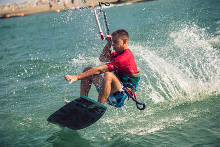 Professional kiter makes the difficult trick on a river. Kitesurfing Kiteboarding action photos man among waves quickly goes 版權商用圖片