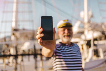Mature man stands on pier dressed in a sailor's shirt and hat using smart phone. Focus on phone. Stock Photo