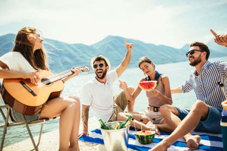 Group of friends with guitar having fun on the beach. Standard-Bild