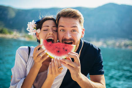 Young smiling couple eating watermelon on the beach having fun Archivio Fotografico