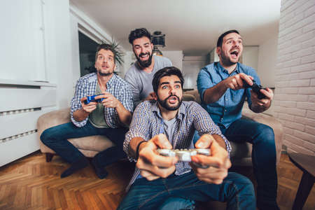 Smiling male friends playing video games at home and having fun. Foto de archivo
