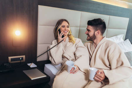 Couple calling room service for food from hotel room