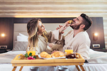 Smiling couple having breakfast in bed in hotel room