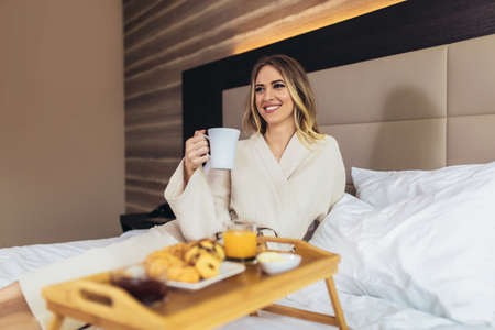 Relaxed Woman Having Breakfast in Bed, home or hotel room