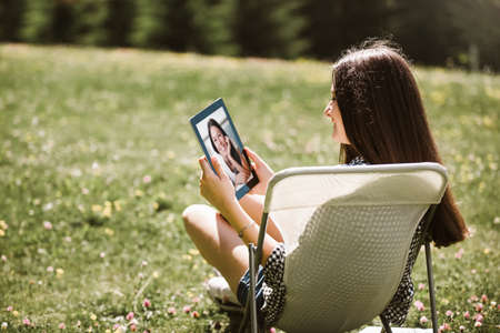 Young girl having video call on digital tablet while resting in park outdoors, enjoying summer 版權商用圖片
