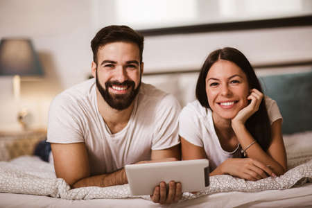 Smiling relaxed young couple using digital tablet in bed at home