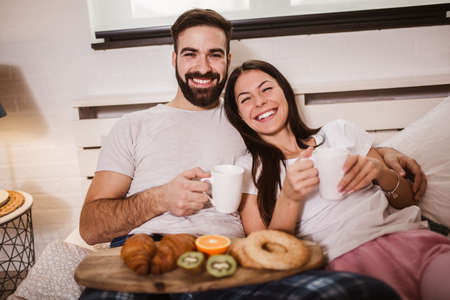 Young happy couple drinking coffee in bed at morning 版權商用圖片