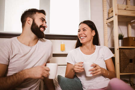 Smiling young couple in bed drinking coffee and looking each other. 版權商用圖片