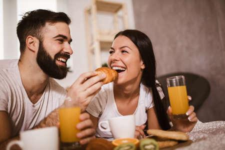 Cute couple having breakfast in bed in the bedroom
