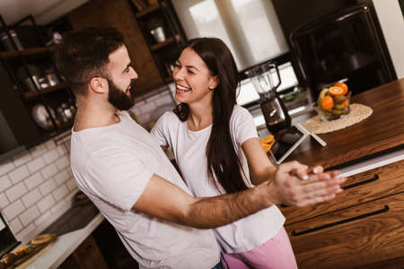 Joyful couple have fun dancing in the kitchen at home in the morning