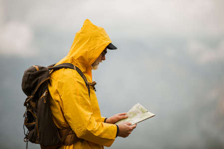 Middle age man traveler in raincoat and backpack using map on hiking