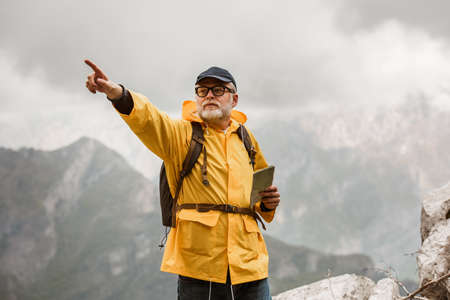 Middle age man traveler in raincoat and backpack enjoying view of mountains. 版權商用圖片