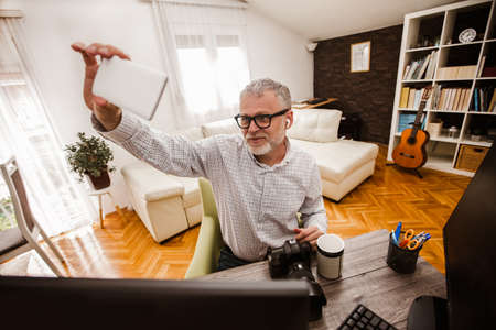 Mature man working from home office make selfie photo, using computer.