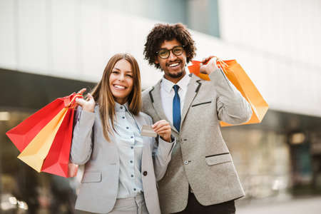 Couple in shopping. Happy couple with shopping bags and credit card enjoying in shopping.