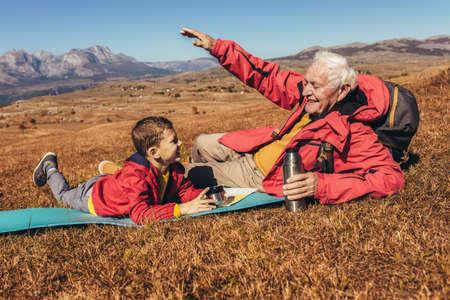 Boy camping with grandfather in autumn, having fun. Stock fotó