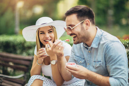 Romantic couple eating an ice cream in the park.