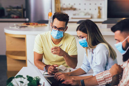 Students studies at home, wear protective masks, and using laptop Stock Photo