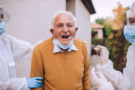 Doctors in a protective suit taking swab from a senior man to test for possible coronavirus infection. Taking corona virus test sample at home concept, senior man in quarantine.