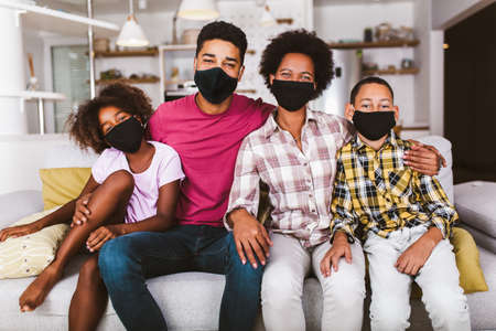 African American parents and cute small kids wearing protective masks at home. Stop the virus and epidemic diseases. Zdjęcie Seryjne