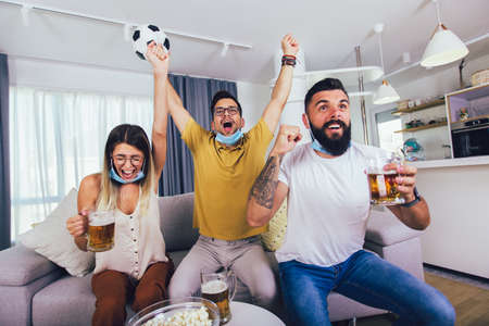 Group of young friends watching a football match at home, cheering and drinking beer, wearing protective mask.