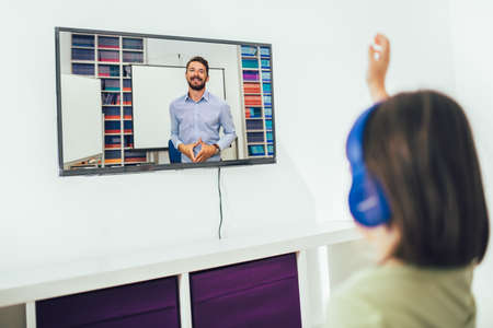 Girl sit and watch the learning and teaching of teachers from the smart TV screen in the house.